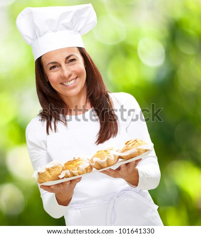 portrait of pretty middle aged cook woman against a nature background - stock photo