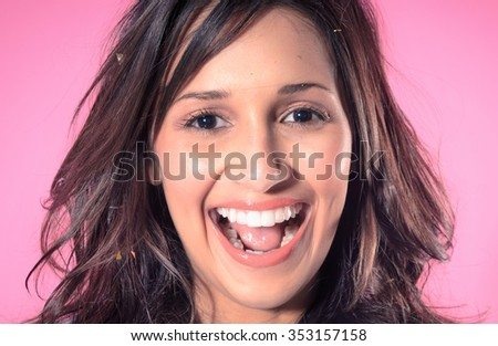 Portrait of pretty mixed race woman with confetti in her hair, smiling and laughing towards camera on pink background