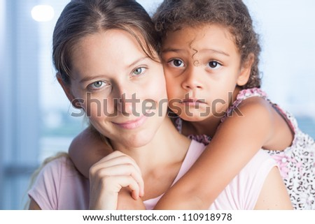 Portrait of pretty mother and daughter looking at camera - stock photo