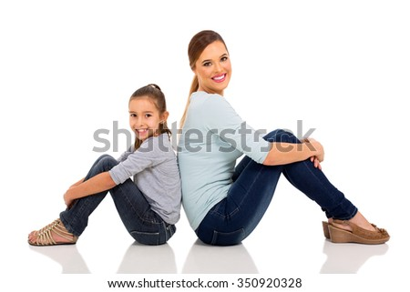 portrait of pretty mother and daughter sitting back to back on white background - stock photo