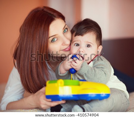Portrait of pretty mother and her little baby son playing at home - stock photo