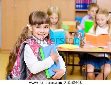 portrait of pretty preschool girl with books in classroom - stock photo