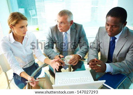 Portrait of pretty secretary explaining something to her boss and colleague