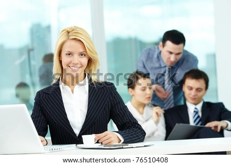 Portrait of pretty secretary looking at camera in working environment