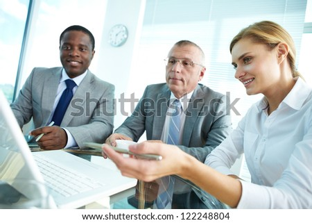 Portrait of pretty secretary pointing at laptop screen while explaining something to her boss and colleague - stock photo