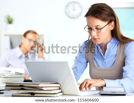 Portrait of pretty secretary typing in office - stock photo