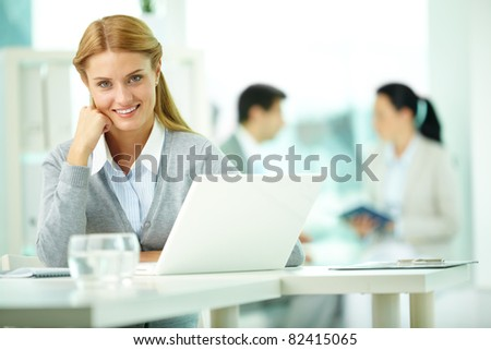 Portrait of pretty secretary working with her partners on background - stock photo