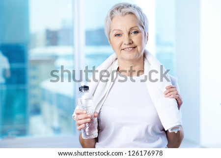 Portrait of pretty senior woman with bottle of water in gym - stock photo
