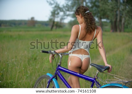 Portrait of pretty sexy young woman in corset and bikini with bicycle on the meadow - Outdoor - stock photo
