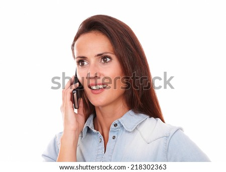 Portrait of pretty single lady on blue shirt speaking on her phone while smiling on isolated studio