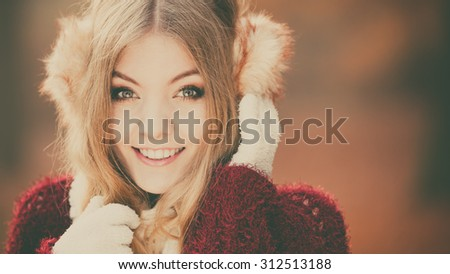 Portrait of pretty smiling fashionable woman in fall forest park. Happy gorgeous young girl in earmuffs and sweater pullover. Autumn winter fashion. Instagram filter. - stock photo