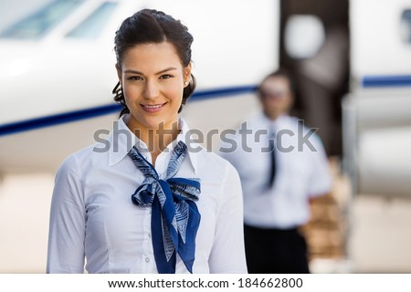 Portrait of pretty stewardesses smiling with pilot and private jet in background at airport terminal - stock photo