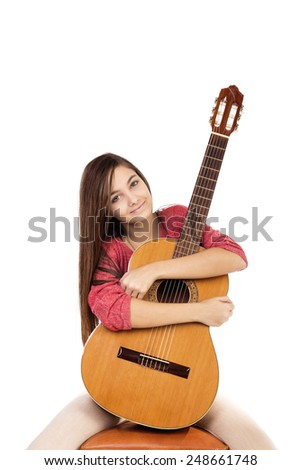 Portrait of pretty teenage girl hugging  her guitar isolated over white background - stock photo