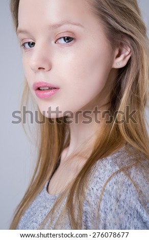 Portrait of pretty teenage girl on gray background