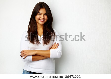 Portrait of pretty teenager standing by the wall - stock photo