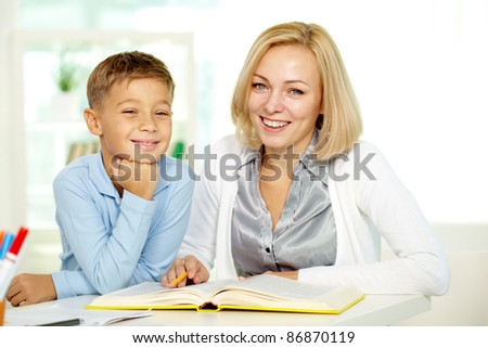 Portrait of pretty tutor and diligent pupil looking at camera with smiles