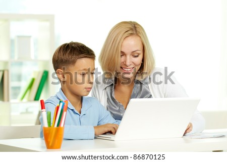 Portrait of pretty tutor and her pupil working with laptop - stock photo