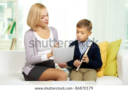 Portrait of pretty tutor showing notes diligent pupil with the flute - stock photo