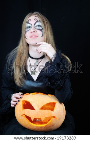 Portrait of pretty vampire girl with halloween pumpkin on black background