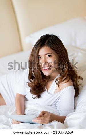 Portrait of pretty Vietnamese girl spending morning in the bed - stock photo