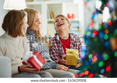 Portrait of pretty woman and her two children sitting at home on Christmas evening - stock photo