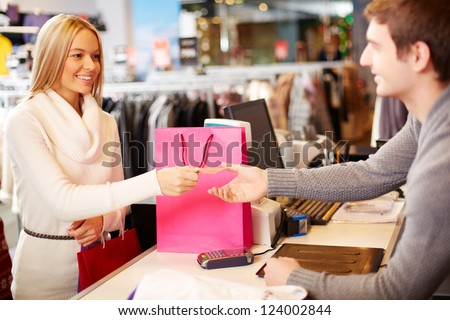 Portrait of pretty woman giving credit card to shop assistant while paying for her purchase - stock photo