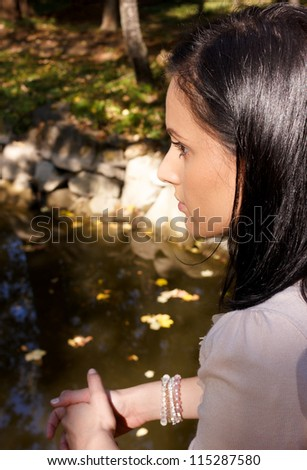 Portrait of pretty woman having a sad expression on her face.River with brown leaves as background. - stock photo
