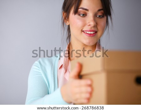 Portrait of pretty woman holding a box  - stock photo