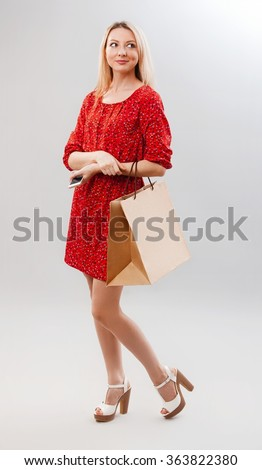 Portrait of pretty woman in red with shopping bag. Female model isolated studio background. - stock photo