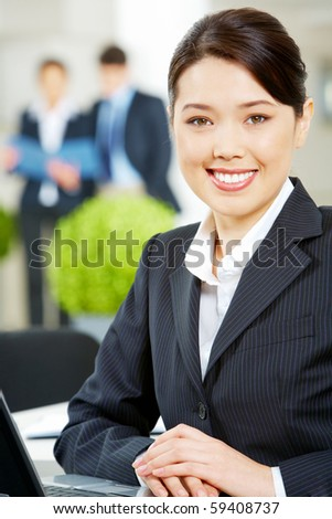 Portrait of pretty woman looking at camera with smile on the background of working partners