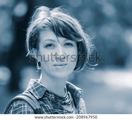 portrait of pretty woman on a background of city park, aged 40 - stock photo