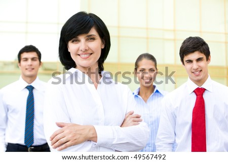 Portrait of pretty woman smiling at camera with business partners at background