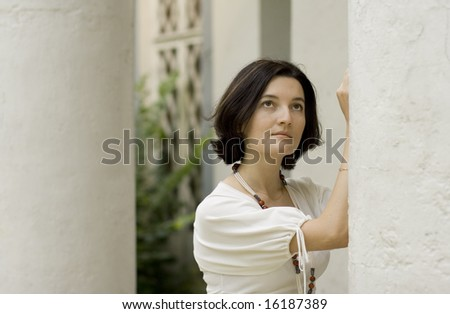 portrait of pretty woman standing near white column