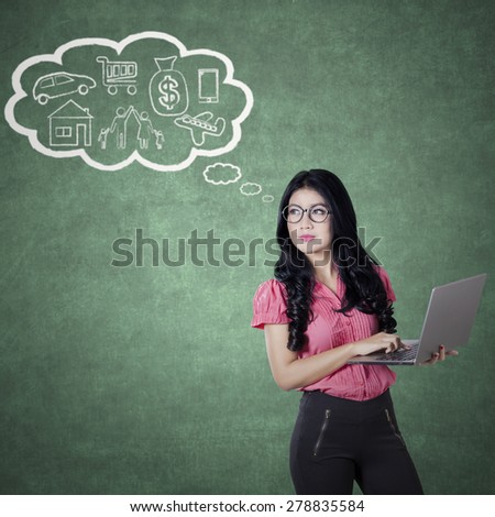 Portrait of pretty woman thinking her dreams while holding laptop computer - stock photo