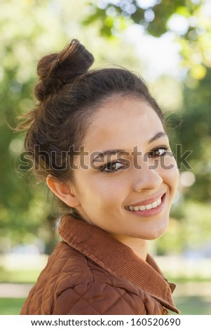 Portrait of pretty woman wearing a coat smiling at camera - stock photo