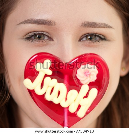 Portrait of pretty woman with candy heart. Love