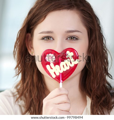 Portrait of pretty woman with candy heart. Love - stock photo