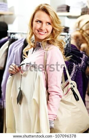 Portrait of pretty woman with fashionable cardigan in clothing department