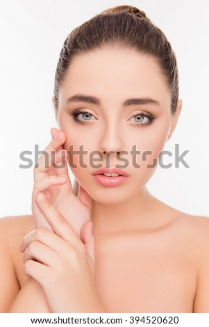 Portrait of pretty woman with perfect skin holding hands near face - stock photo