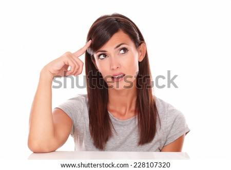 Portrait of pretty woman wondering with her hand on head while looking to her left on isolated white background - copyspace - stock photo