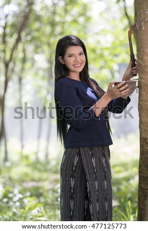 Portrait of pretty young asian woman in rubber plantation,Southern Thailand.