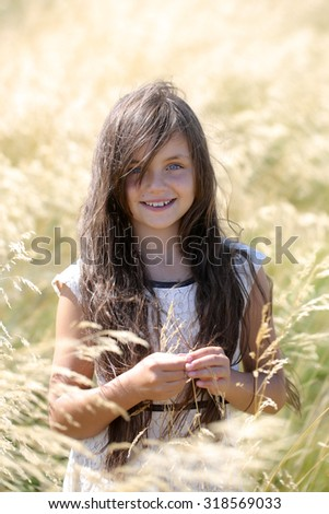 Portrait of pretty young brunette happy girl with long hair in white lace dress looking forward standing in valley among yellow spikelet sunny windy day outdoor, vertical photo