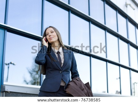 portrait of pretty young business woman talking on phone near building - stock photo