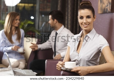 Portrait of pretty young businesswoman drinking coffee, sitting in hotel lobby, smiling, looking at camera. - stock photo