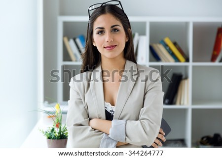 Portrait of pretty young businesswoman looking at camera in the office.