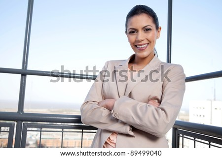 Portrait of pretty young businesswoman smiling with arms crossed - stock photo