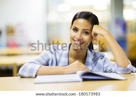 portrait of pretty young college student in library