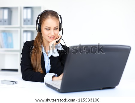 Portrait of pretty young female operator sitting at office desk with headset