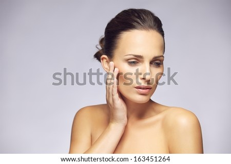 Portrait of pretty young female touching smooth and healthy skin of her face and looking away against gray background. Beautiful woman model with perfect skin. - stock photo