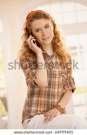 Portrait of pretty young girl at home, smiling using mobile phone, sitting front of window.? - stock photo